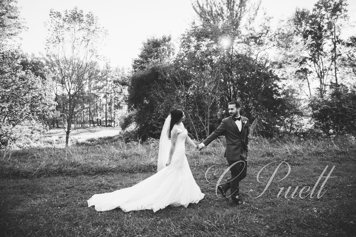 Black and white photo of bride and groom  by the side yard