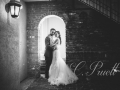 Black and white photo of bride and groom under the archway